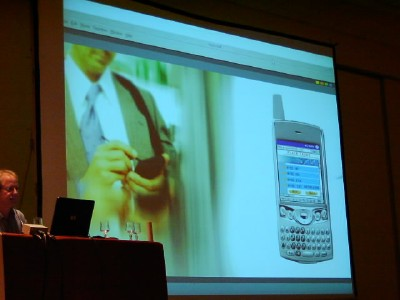 a photo of the screen during phone demo: business man entering data next to a picture of the face of the phone showing the interface to what he is doing
