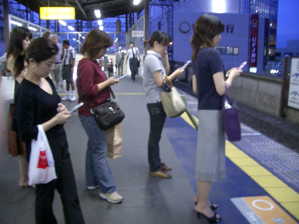 Several people waiting for train and using their mobile phones