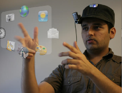 Pranav Mistry using hand movements to control a computer screen that exists only as a projected image in front of him