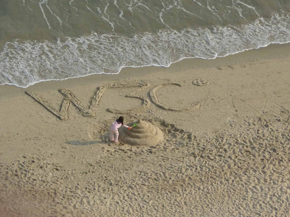 little girl at South China beach playing with a W3C logo sandcastle