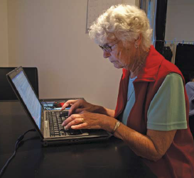 photo of old person typing on laptop