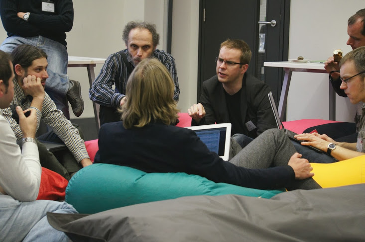 A group of ca. 7 people sitting on bean bags discussing a topic. Jeremy Tandy is making a point