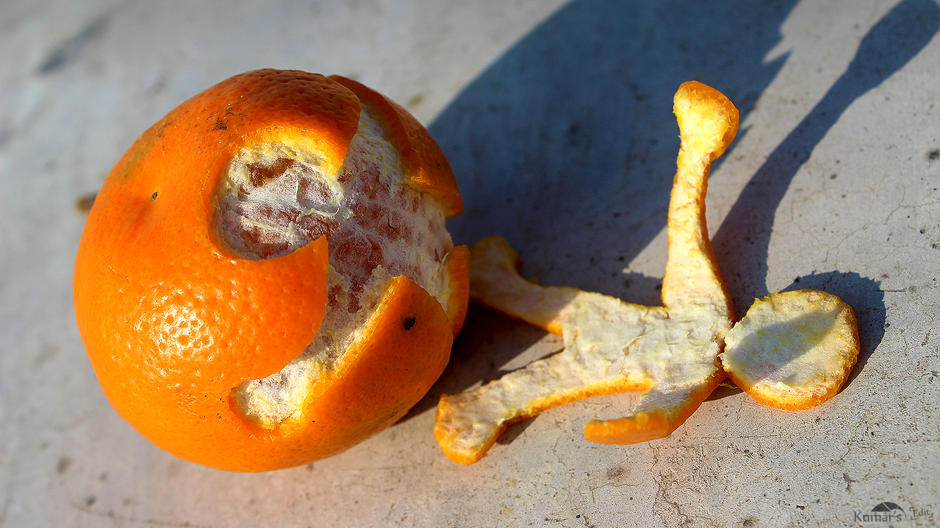An orange with a shape of a person cut out. The cut out shape lies next to the orange.