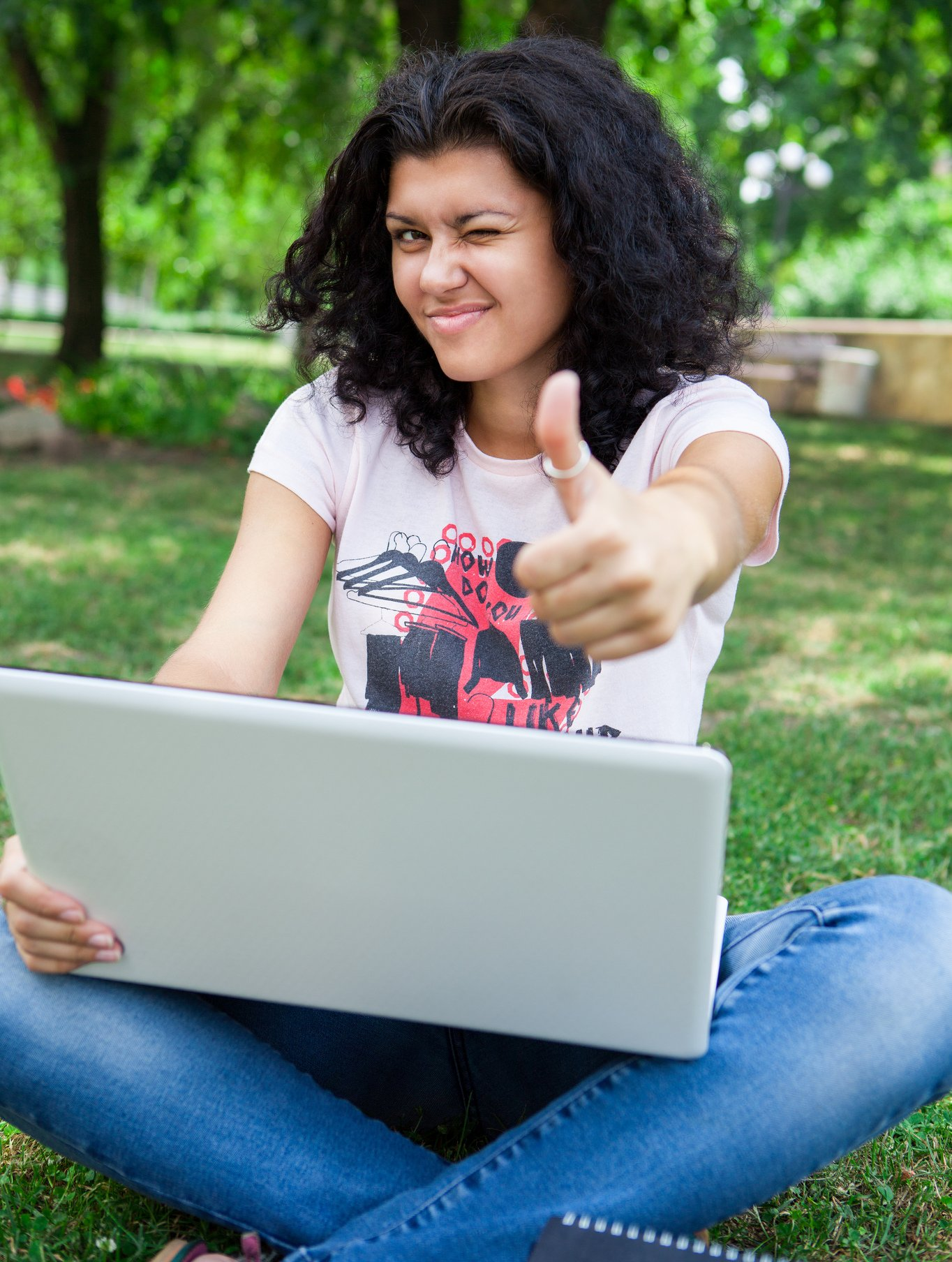 A college girl on her laptop in the park giving the thumbs up sign