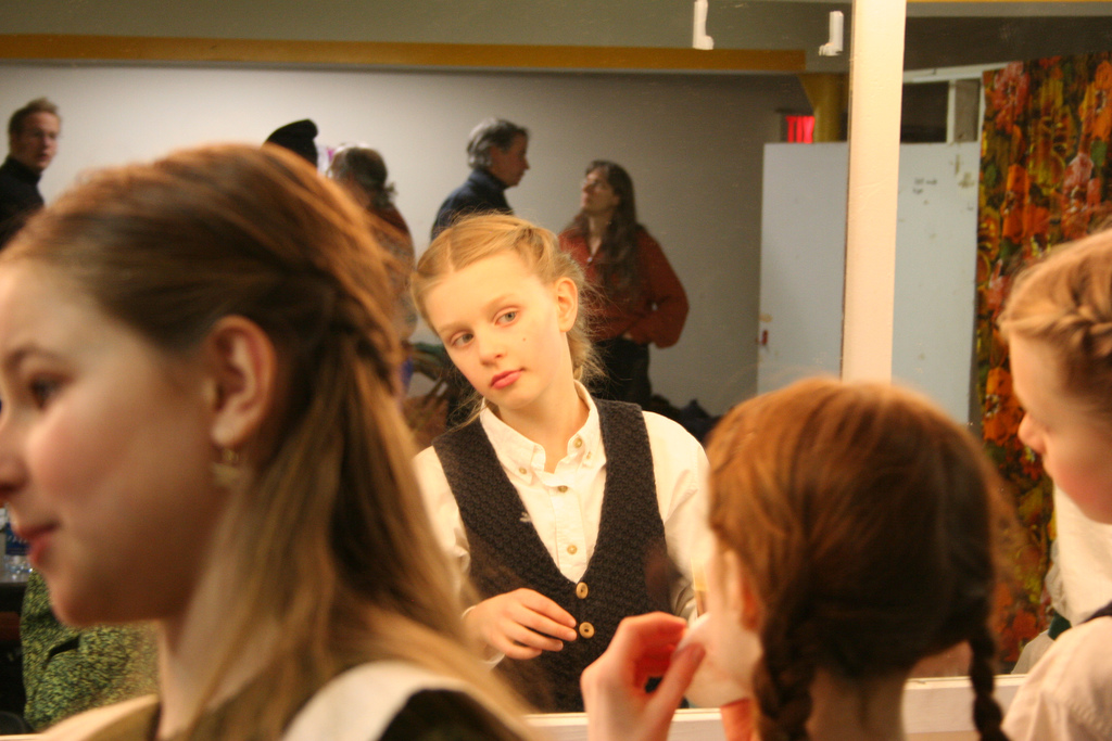 A girl, early-mid-teens, looks critically at herself in the mirror, surrounded by others