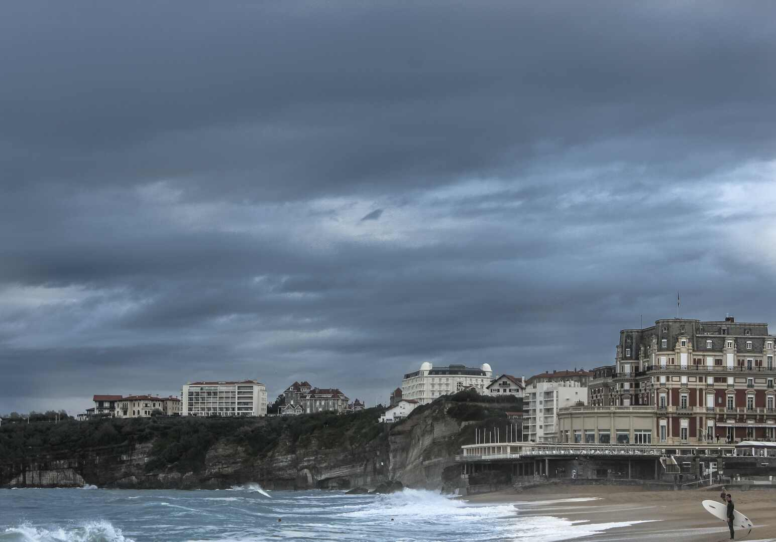 [image: beach, cliffs, buildings, dark clouds and a surfer]