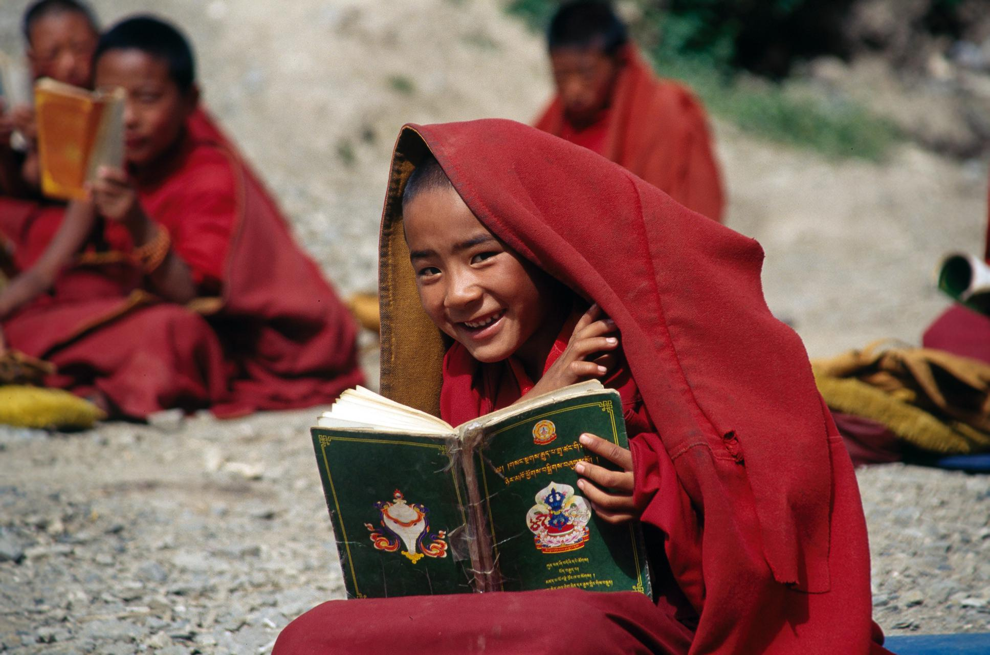 Photo: a boy Tibetan monk, reading a book with Tibetan letters
