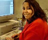 woman wearing casual clothing and smiling, sitting in front of computer