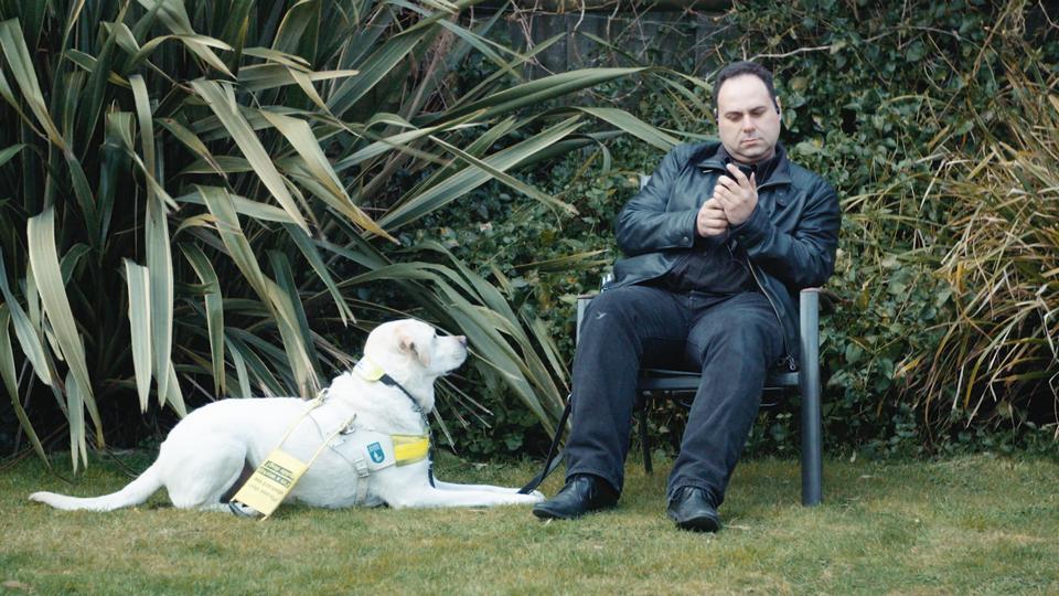 صورة لرجل يحمل جهاز محمول باليد، كلب التوجيهي عند قدميه
