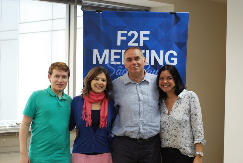 Four people standing in fromt of a roll up poster saying F2F Sao Paulo