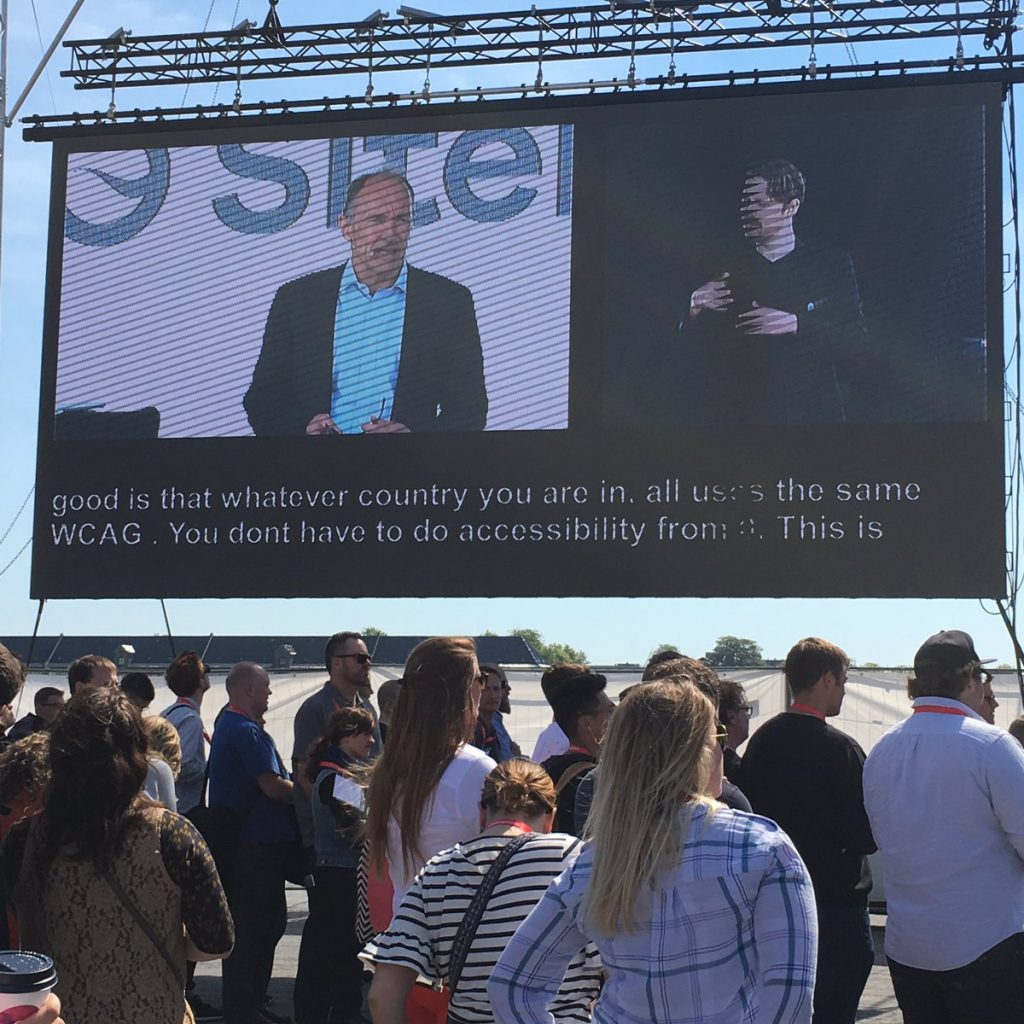 Tim Berners-Lee, text and a sign-language interpreter shown on a screen before an audience at SiteImprove